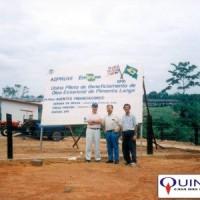 Sr José Azambuja (ao centro) da QUINARÍ no estado do Acre em 1997, onde participou ativamente do Projeto da Pimenta Longa por mais de 15 anos. Ao fundo, a placa da usina piloto de beneficiamento de óleo essencial, Embrapa (Brasil) e DFID (Inglaterra).